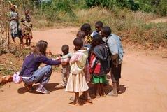 Une visite femelle volontaire de docteur un enfant africain Photographie stock libre de droits