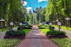 Une voie avec des plantations des buissons et des lanternes par des balles des côtés, mène au monument du mémorial photos stock