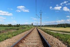 Une voie de chemin de fer électrifiée parmi les prés et les champs de blé verts Un jour ensoleillé avec un ciel bleu clair avec d Photo stock