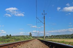 Une voie de chemin de fer électrifiée parmi les prés et les champs de blé verts Un jour ensoleillé avec un ciel bleu clair avec d Photos stock
