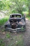 Une voiture abandonnée sur un chemin dans les bois Photo stock
