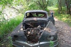 Une voiture abandonnée sur un chemin dans les bois Image stock