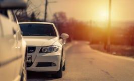 Une voiture blanche au coucher du soleil attendant pour aller sur une petite promenade images stock