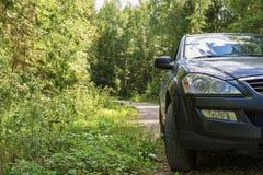 Une voiture foncée a garé du côté d'une route de campagne dans les bois Photo stock
