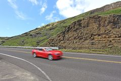 Une voiture rouge sur une des routes hawaïennes Photo libre de droits
