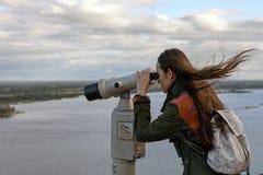 Une voyageuse de jeune femme sur la plate-forme d'observation regardant par des jumelles le panorama de la ville de Nijni-Novgoro images stock