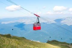 Une vue à la carlingue ouverte de benne suspendue de rouge au-dessus du dessus de la montagne a Photo libre de droits