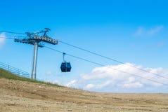 Une vue à une carlingue moderne bleue de benne suspendue se déplaçant au dessus du Images libres de droits