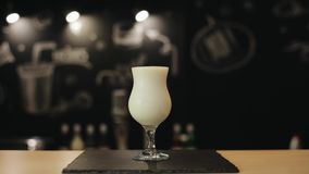 Une vue étroite d'un verre plein du milkshake sur un compteur de barre Main masculine de barman mettant deux pailles dans la bois banque de vidéos
