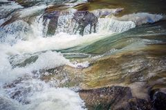 Une vue étroite d'une petite rivière rapide de montagne dans le mouvement Images stock