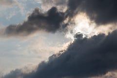 Une vue étroite de quelques nuages déprimés et grands avec la moitié du soleil c Photographie stock libre de droits