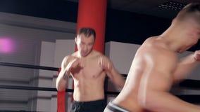 Une vue étroite sur deux combattants de torse nu se donnant un coup de pied banque de vidéos