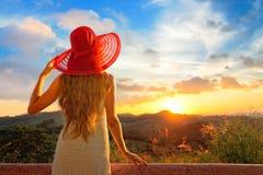 Une vue d'arrière sur un coucher du soleil de observation de jeune femme merveilleuse Image stock