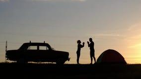 Une vue d'une silhouette d'un couple affectueux, qui battent leurs mains contre le coucher du soleil banque de vidéos