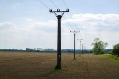 Une vue d'une rangée des colonnes d'une colonne de ligne électrique dans un paysage avec des arbres avec un champ Image stock