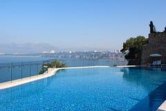 Une vue de la piscine et la mer avec la turquoise dégagent l'eau avec une gamme de montagne sur l'horizon et la ligne du méditerr Photographie stock