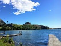 Une vue du dock à travers un beau lac seul à un hôtel majestueux sur la colline photo libre de droits