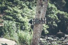 Une vue horizontale de signe en bois fait main classique de conception simple de toilette donnent la direction à la carte de trav photo libre de droits