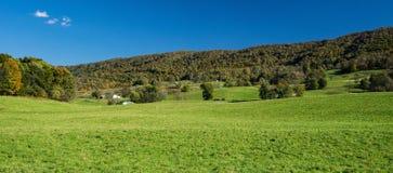 Une vue panoramique d'une ferme à la base de la montagne de descente de crique photos stock