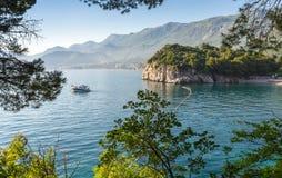 Une vue par les arbres à la mer et aux montagnes Photo libre de droits