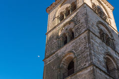 Une vue romantique d'une tour à Trujillo avec la lune apparaissant dans la lumière du jour simple Photos libres de droits