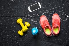 Une vue supérieure des entraîneurs roses, de la bouteille pour l'eau, du téléphone et des petits dumbells sur un fond noir Folâtr Images libres de droits