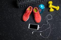 Une vue supérieure des entraîneurs, sports mettent en bouteille, téléphone et haltères sur un fond noir Folâtre des accessoires C Photos stock