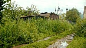 Une vue sur le petit village - vieille maison et chemin humide sur un premier plan - grande église sur un fond - Suzdal, Russie clips vidéos