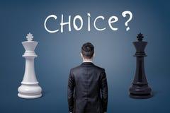 Une vue sur un dos du ` s d'homme d'affaires comme il se tient entre deux rois d'échecs et un choix de lettrage Photographie stock libre de droits