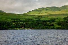 Une vue vers le loch Tay loge le village pris du bateau de location dans un lac, Ecosse centrale Photographie stock libre de droits