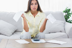 Uneasy woman doing her accounts. Sat on a couch Royalty Free Stock Image