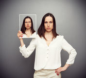 Unemotional woman hiding her doubt. Concept photo over dark background Stock Photos