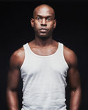 Unemotional young black man in tank top. Single serious young black man with shaved head and penetrating expression in white tank top over dark background Royalty Free Stock Photo