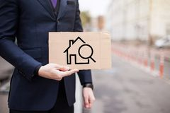 An unemployed businessman holds a cardboard sign with the image of a house, renting and buying royalty free stock photos