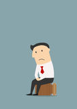 Unemployed cartoon businessman after dismissal. Depressed fired cartoon businessman sitting on a suitcase after dismissal. Unemployment theme concept Stock Photos