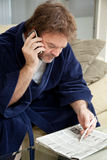 Unemployed Looking for Job. Unemployed man looking through the job listings and making phone calls royalty free stock image