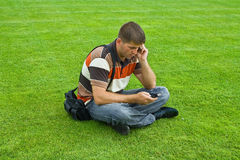 Unemployed looking for work. Young unemployed man makes phone calls in search of work, sitting on the green grass Royalty Free Stock Photography