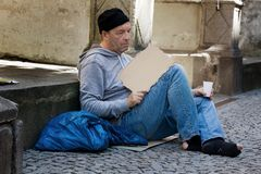 Unemployed looking for work. A homeless person looking for new work. Arbietsloser beggars living on the street Royalty Free Stock Photo