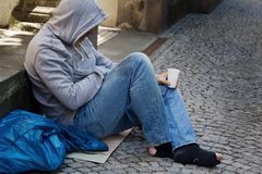 Unemployed looking for work. A homeless person looking for new work. Unemployed beggars living on the street Stock Image