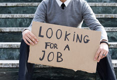 Unemployed man. Young businessman holding sign Looking for a job Royalty Free Stock Photo