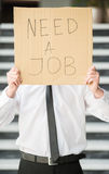 Unemployed man. Close-up of man in suit holding sign in hands. Unemployed man looking for job Stock Photo