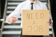 Unemployed man. Close-up of man in suit holding sign in hands. Unemployed man looking for job Stock Images