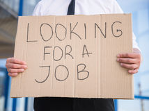 Unemployed man. Close-up of man in suit holding sign in hands. Unemployed man looking for job Stock Image