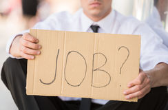 Unemployed man. Close-up of man in suit holding sign in hands. Unemployed man looking for job Stock Photos