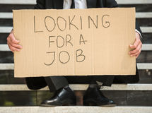 Unemployed man. Close-up of man in suit sitting at stairs with sign in hands. Unemployed man looking for job Royalty Free Stock Photography