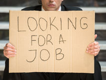 Unemployed man. Close-up of man in suit sitting at stairs with sign in hands. Unemployed man looking for job Royalty Free Stock Image