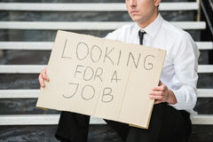 Unemployed man. Close-up of man in suit sitting at stairs with sign in hands. Unemployed man looking for job Stock Photos