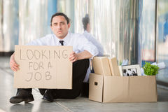 Unemployed man. Fired frustrated man in suit sitting near office with sign Stock Image