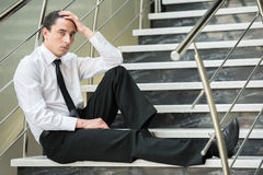 Unemployed man. Fired frustrated man in suit sitting at stairs in office Stock Images