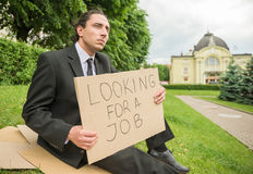 Unemployed man. Frustrated unemployed man with sign sitting at the lawn Royalty Free Stock Photo